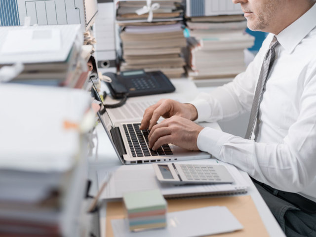 Businessman working on laptop surrounded by mounds of paper