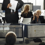 Workers in office looking at computers in open layout