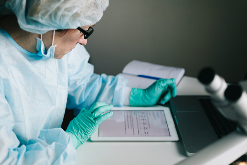 Scientist in protective gear looking at tablet