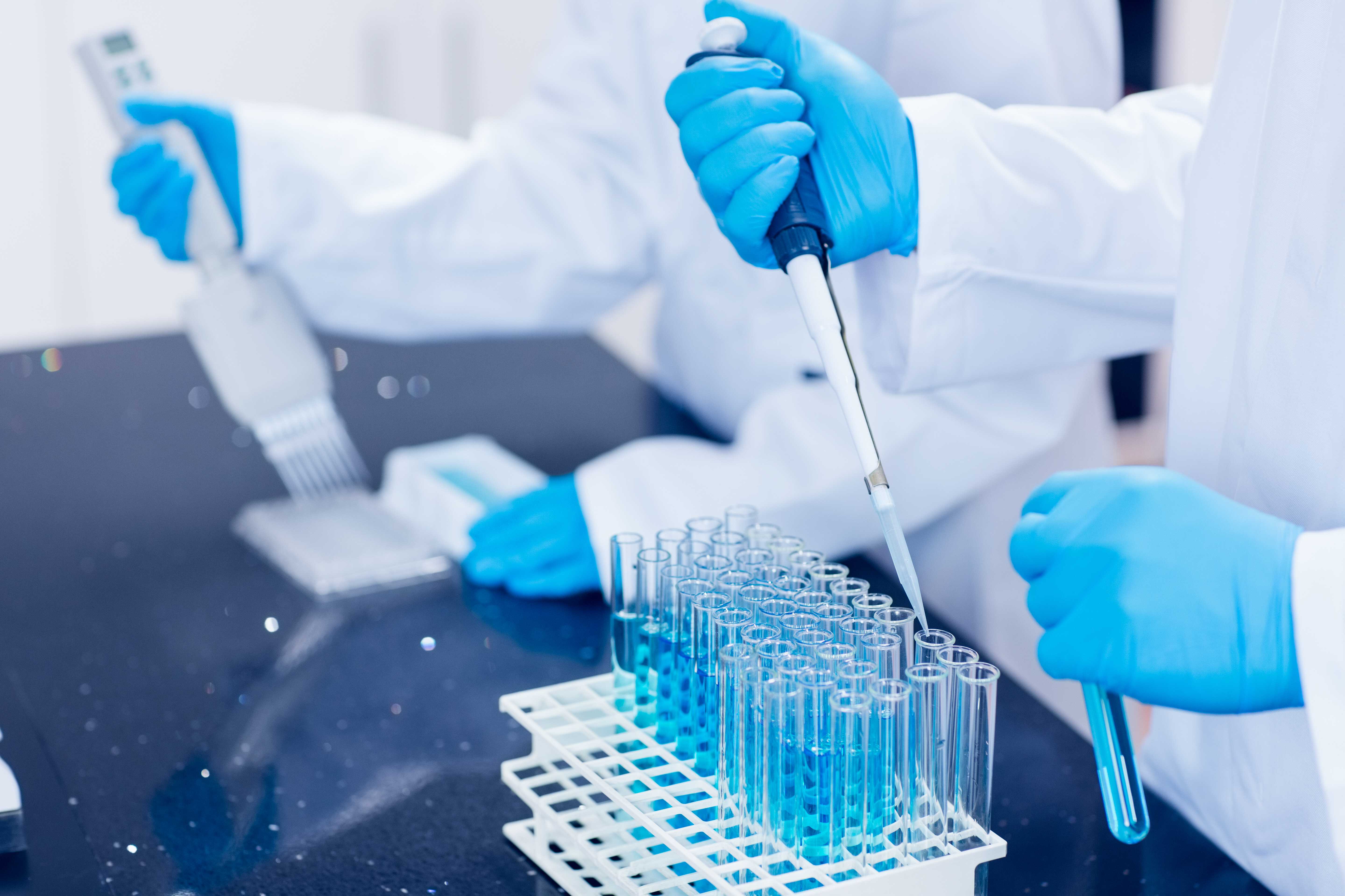 Scientists using pipettes in lab test, life sciences