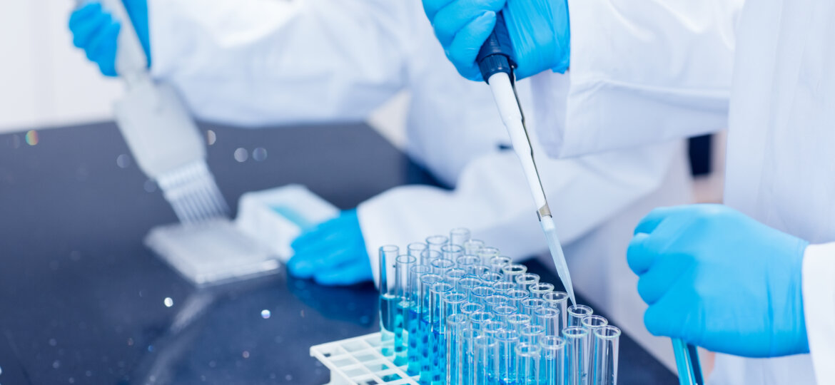 Scientists using pipettes in lab test