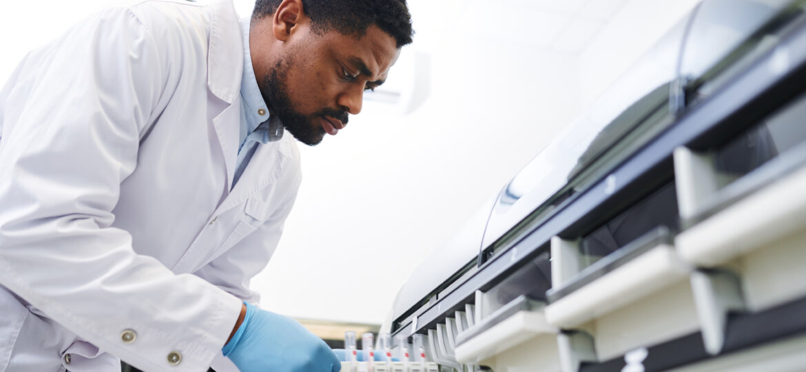 Black doctor working with pharmaceutical machine