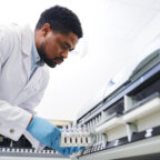 Serious concentrated young black male doctor with beard wearing lab coat and sterile gloves working with pharmaceutical machine and putting samples into it